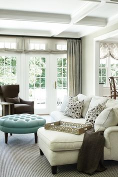 living room - round tufted turquoise blue ottoman ivory sofa chaise lounge chocolate brown wingback chair gray ribbed rug coffered ceiling wall French doors transom windows gray sheers