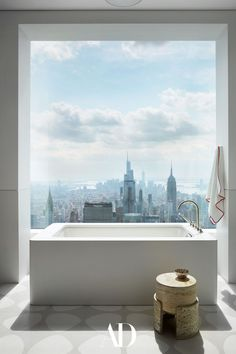 Up in the clouds, this luxurious Manhattan bathtub is the star of the show. Fusing simplistic and elegant design with stunning views of the New York City, this bathroom is a dream. #bathroom #bathtub #white #simplistic #minimalism #views #manhattan #skyline #windows #tile Architecture Design, Solid Oak Doors, Manhattan Apartment, Entry Hall, Step Inside, Stone Flooring, House Goals, Architectural Digest, Bathroom Interior Design