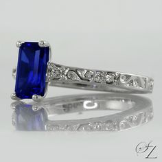 A beautiful ring! An incredible emerald cut Tanzanite glowing with wonderful vivid blue shards set as a solitaire in a gorgeous filigree detailed band with delicate Diamond accents that add that extra little sparkle and catch the eye.