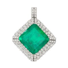 White Gold, Emerald and Diamond Pendant   14 kt., centering one square-shaped emerald-cut emerald approximately 26.85 cts., framed by 80 round diamonds approximately 4.00 cts., approximately 10.8 dwt.