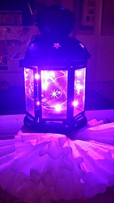 IKEA lantern with purple string lights, sitting on a dollar store styrofoam cube, decorated with coffee filters.