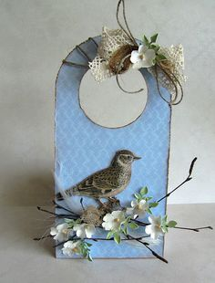 my paper land. Bird with very realistic paper flowers and foliage on a blue tag.