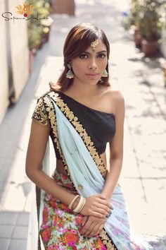 Black raw silk one-shoulder blouse with a shoulder strap, Raw silk floral skirt and pastel blue soft net dupatta