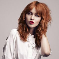Ginger red medium wavy tousled hair style with bangs fringe parting