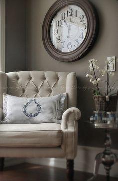 khaki walls. clock. chair. silver table.