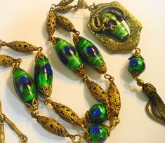 """Very rare and fine early Czech Foiled Peacock Bead Glass Sautoir Necklace. This is a really beautiful old necklace probably dating from about 1920 - 1930, Edwardian to Art deco eras. This is a lovely necklace with large shimmering green foiled beads with luminous deep cobalt blue """"Eyes"""". Pendant features a fierce dragon dragon protectively curled around an oval peacock eye bead."""