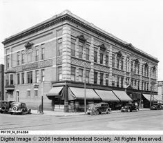 Swope Building Exterior. 	The Swope Building in Terre Haute took up a city block. Awnings are on the windows. Automobiles are parked along the curbs. 1935. Is this where the Swope Art Museum is now?