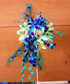 peacock feathers and orchids.  so exotic!  Goota figure out that deep blue flower. most likey a dyed plant... whatevs looks awesome!