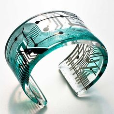 """Paola Mirai designed this """"Cirkuita"""" line of jewelry by encasing pieces of old electronics in glass or resin. SO AMAZING!"""