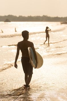 Silhouette of surfer on beach with surfboard. by kasto80