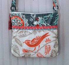 Fun mix of bird canvas and tribal upholstery fabric come together in this boho crossbody bag. Trim accents. Zipper top with floral inside lining and a pocket. Contrasting back with a big pocket for easy access to cell or keys. Measures 11 X 11 . Boho crossbody bag easy to wear and goes