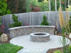 Interlocking paver surround with custom fire pit and stone seating wall, designed and installed by Graham Landscape and Design