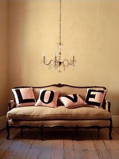 Love pillows in nearly bare living room (love the couch and chandelier though)  via ♫ La-la-la Bonne vie ♪