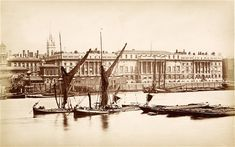 This picture shows Custom House, one of London's best surviving examples of 19th-century architecture, viewed from the river circa 1875. Part of Billingsgate market can be seen on the left; the crane is probably being used to demolish the old building, and help construct the new market.