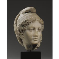 A MARBLE HEAD OF GANYMEDE, ROMAN IMPERIAL  , CIRCA 1ST CENTURY A.D.  or perhaps Paris, probably inspired by a Greek sculpture of the 4th Century B.C., the youth turned to his left, his centrally parted wavy hair falling in drilled spiral curls over the temples and surmounted by a Phrygian cap with ends tied in a bow on the crown, long spiral curls falling over the nape of the neck. Height 8 1/2 in. 21.6 cm.