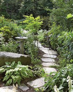 Rock can make digging difficult, but it ensures a steady supply of stone for working into garden design, as shown in this simple path cutting through a perennial bed.