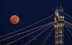 A plane passes the full moon as it rises over Albert Bridge on February 7, 2012 in London