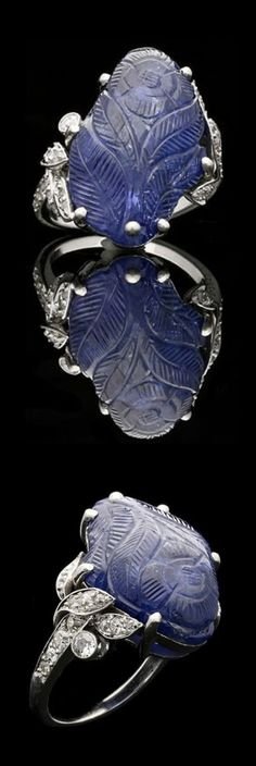 Cartier - A beautiful and unusual Art Deco carved sapphire and diamond ring, circa 1925. Set with an irregular shaped cabochon sapphire which has been carved with a single flower on a stem with four leaves, between asymmetric foliate diamond set shoulders, all in platinum to a finely tapered shank.