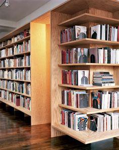 Encadrant la porte d'entrée, la longue bibliothèque couvre tout un pan du loft.