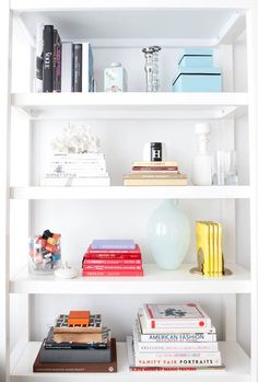 stylish bookcase.  i like the idea of placing books by colour along with other visually interesting knickknacks.