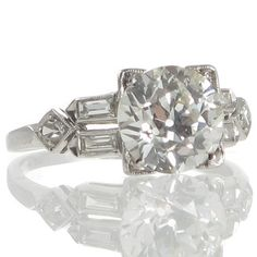A platinum Art Deco ring featuring a 2.25ct transition cut diamond set in four corner claws that taper down the box style gallery between slightly upswept shoulders each with a pair of baguette cut diamonds set in spaced individual bezel mounts along the length of the shoulders each pair meeting a kite shaped diamond set mount as the shoulders taper to the plain polished band. #RutherfordJewellery #Melbourne