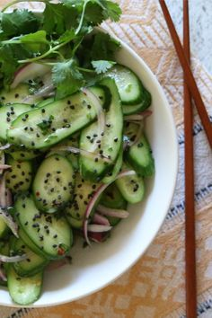 Asian Cucumber Salad - Thinly sliced cucumbers and red onions tossed with a white wine vinaigrette dressing makes a light and refreshing salad. Top with rich black sesame seeds for major flavor action. Paleo & Whole 30 Compliant.