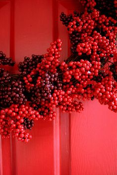 Wreath of red & dark purple on a red door...pretty
