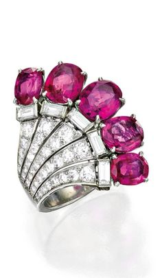 An Art Deco Platinum, Pink Sapphire and Diamond Ring, Circa 1935. The fan-shaped motif set with five cushion and oval-shaped pink sapphires weighing approximately 7.20 carats, accented by numerous old European, single-cut and baguette diamonds weighing approximately 1.50 carats.
