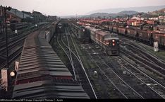4th Street, Altoona, Pennsylvania, on 15 August 1964. Shown here are four freight trains parked in the Altoona Yards, all awaiting crews so that they can begin climbing the Allegheny Mountains via the Horseshoe Curve to Gallitzin and points West. Also visible on the left are two passenger cars awaiting reconditioning in the PRR's Passenger Car Shops behind them. This photo taken from the 4th Street Bridge.