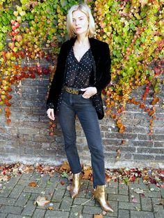 A sheer polka dot blouse is paired with a black blazer, jeans, a Moschino belt and metallic booties.