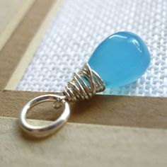 An aqua blue chalcedony gemstone briolette wire wrapped in sterling silver wire. It includes a 6-7mm jump ring.    My dangle charms can be easily
