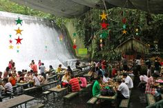 Villa Escudero with the Waterfalls Restaurant, Quezon Province, Philippines.....Lunch is served against an impressive backdrop of thundering clear spring water. Grass fringed buffet stations and bamboo dining tables stand steadily in just inches of flowing river water from the sparkling falls, as it washes around the feet of diners enjoying delicious local dishes