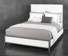 The Mason upholstered iron bed uses a simple but impressive squared-off silhouette. With a lofty headboard and atop a minimalist square frame, the use of leather accents soften edges.