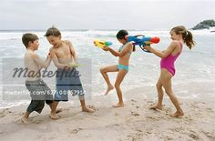 Children playing with water pistols at the beach - Stock Photos