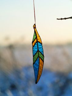 ➳ This feather made from glass Spectrum  All details cut, foiled and soldered carefully by us.  It can become a beautiful decoration for the window, terrace or varanda, and also it can be a personal mascot for you.  Size: ► Lengh: 17 cm /6.7 ► Width: 3 cm / 1.5 ► Weight: 53 g. ► Number of pieces: 9  ► Stiches are black patina, covered with aftersoldering composition ► On waxed cord 50 cm  In stock there are 4 items. The price is for one feather.  ✴️ Recommendations for care: - Keep away from…