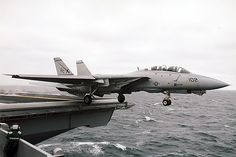 """An F-14 Tomcat from VF-32 """"The Swordsmen"""" roars off the flight deck of the U.S.S. Enterprise, CVN-65, into a rainy sky out in the Atlantic Ocean."""