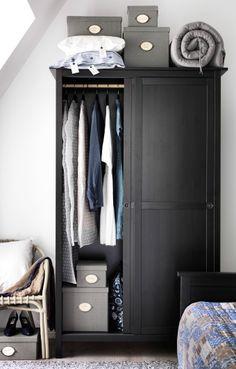 Vista de um closet com portas deslizantes e móveis e acessórios IKEA.