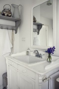white on white bathroom. Love the shelf idea on wall and hanging pearls.    Like idea of making border aroumd countertop