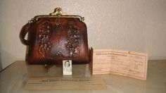 Antique- 1930's Tooled leather purse with a gold metal clasp. This purse was owned by Lucy Evans a teacher at North Texas State College and sister of Dr. Mary Elizabeth Evans the first woman to earn a doctoral degree from North Texas State College.  http://enchanteddecorations.com/contact.php