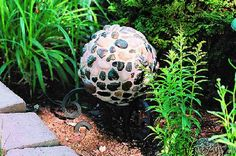 Bowling ball garden art projects are a fun way to display your garden style. Create this craft with river rock, or use mirror tiles or sparkling gems.