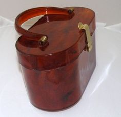 Brown Tortoise Shell Purse  The beauty of this classic circa-1950s Lucite purse is in the color – a warm tortoise shell brown accented with brass-colored hardware and clasp.  This box shape was very popular for both evening and daytime use.