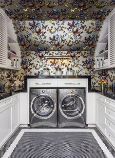 Contemporary laundry room features ceiling & walls clad in Christian Lacroix Butterfly Parade Wallpaper lined  w/a front load silver washer & dryer tucked under built-in cabinets illuminated by a picture light.