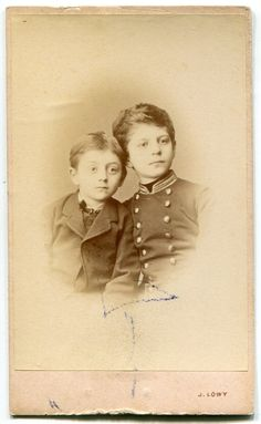 Old visit portrait Austria 1900's: two boys, one in military-style uniform. Huge eyes, cute hairstyle.  ORIGINAL vintage photo by PhotoMemoriesLane on Etsy