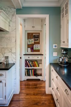 good color with marble tile, white cabinets and dark counter, wood floor