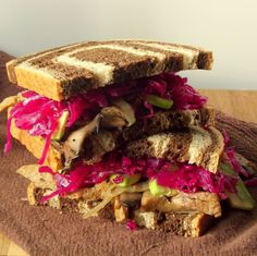 Vegan seitan reuben sandwiches made from sautéd seitan with mushrooms and onions, topped with sauerkraut and avocado slices.