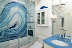 A cramped bathroom with lots of character, designer Clifford Scholz was able to create a sophisticated, coastal look with what little space he had. A shimmering chandelier and a stunning mural add decoration without taking up space.