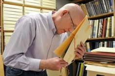 University Archivist Barry Cowan inspects the date on a photograph Monday, Mar. 2, 2015, in his office in Memorial Hill Library.