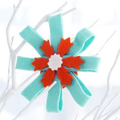 For instant elegance, decorate your Christmas tree with handmade felt rosettes. The beautiful Christmas ornaments will add a wintry effect to your decor.  /