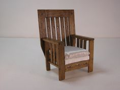 Arts and crafts chair. With a white silk cushion. Made in obeche wood varnished to oak. Size is 95 mm high x 61 mm wide x 55 mm deep.