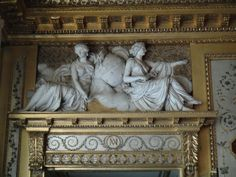 """Château de Fontainebleau. Urania (Astronomy) with a celestial globe and a compass, and a mystery woman with a caduceus (perhaps Melpomene, the muse of tragedy?) The silver boudoir (""""boudoir argent"""") was decorated by the Rousseau brothers in 1786 in the antique style. The room features four pairs of overdoor sculptures, representing female personifications of various arts and sciences, such as music, theater, and astronomy. Each figure holds the attributes of one or two of the nine muses."""